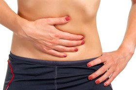 Woman suffering from stomach pain, isolated in white.