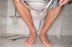 Close_up of man sitting on toilet reading magazine