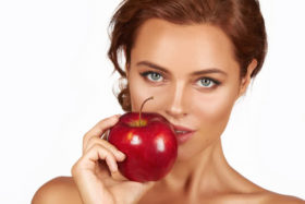 Young-woman-holding-big-red-apple-to-enjoy-the-taste