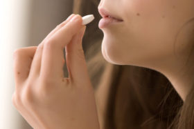Close up image of woman drinking round white pill