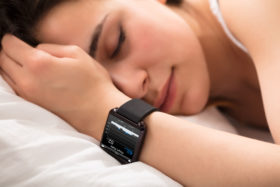 82978066 - woman sleeping on bed with smart watch showing heartbeat monitor