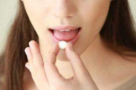 Beautiful young woman taking pill, closeup